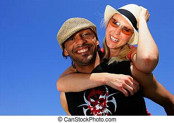 Man giving girlfriend piggy-back at the beach