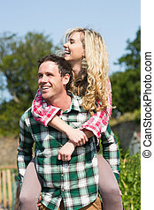 Man giving his beautiful girlfriend a piggyback ride in...