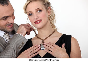 Man giving his girlfriend a necklace