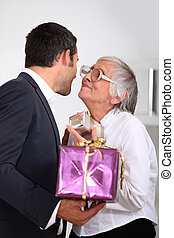Man giving his mother gifts
