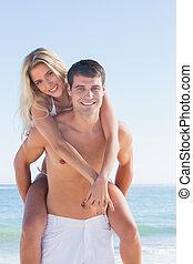 Man giving his pretty girlfriend a piggy back at the beach