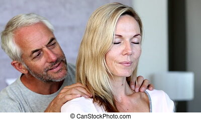 Man giving partner a shoulder rub at home in the bedroom