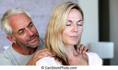 Man giving partner a shoulder rub