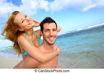 Man giving piggyback ride to girlfriend at the beach