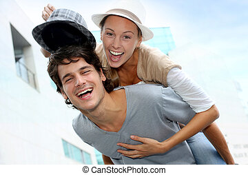 Man giving piggyback ride to girlfriend