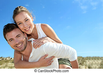 Man giving piggyback ride to girlfriend on a sand dune