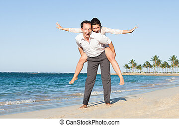 Man Giving Piggyback Ride To Woman At Beach