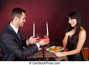 Man giving present to a woman in restaurant