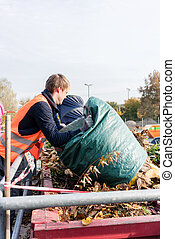 Man giving waste green in container on recycling center...