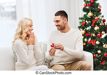 man giving woman engagement ring for christmas - love,...