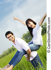 meadow - Man giving woman piggyback in meadow, laughing. ...