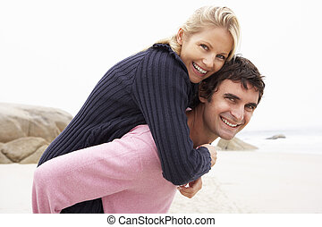 Man Giving Woman Piggyback On Winter Beach