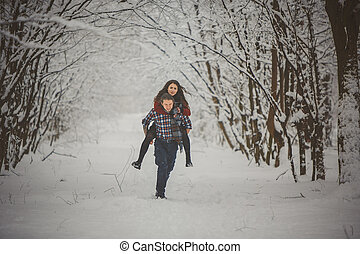 Man giving woman piggyback ride on winter vacation in snowy forest
