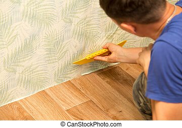 Man glues the wallpaper to the wall in the house