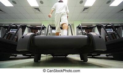 man goes on treadmill in big empty gym