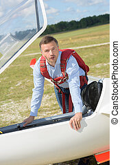 man going inside the glider aircraft