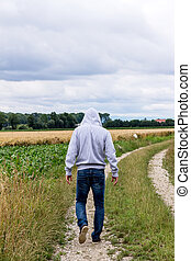 man going on road - a man walks on a lonely road.