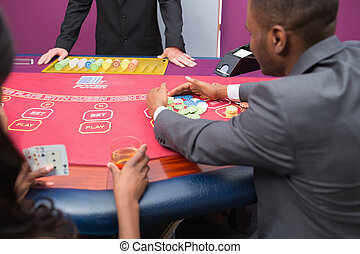 Man grabbing chips at poker table