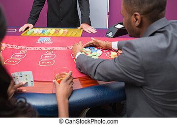 Man grabbing chips at poker table