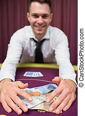 Man grabbing money at poker table