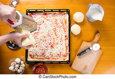 Man grating cheese on pizza base