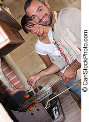 Man grilling sausages on an indoor barbecue