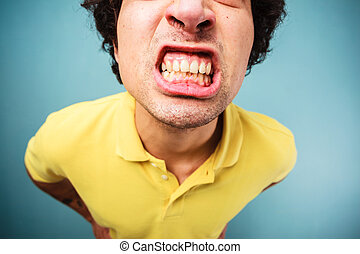 Man grinding his teeth - Young man is grinding his teeth and...