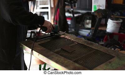 Man doing metal work grinding metal surface