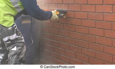 Man grinding mortar using grinder - Bricklayer, man wearing...