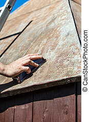 Man grinding the roof of a garden shed with a sanding block, rust and weathered