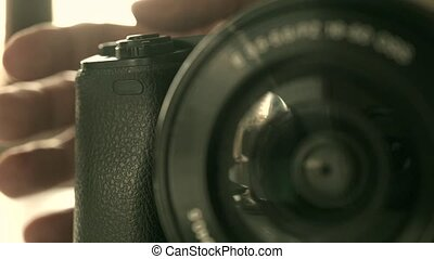 Man grips mirrorless photo camera macro shallow focus video...