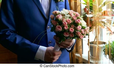 man groom lifts bridal bouquet at wedding table accessories...