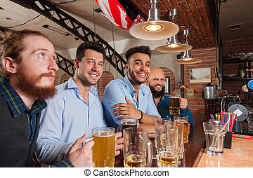 Man Group In Bar Hold Glasses Happy Smiling, Drinking Beer, Mix Race Cheerful Friends Meeting