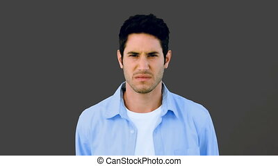 Man growling at camera angrily on grey background in slow...