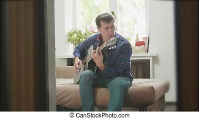 man guitarist playing music by wooden acoustic guitar. Man Playing Acoustic Guitar Close Up slow motion video. in the room sits on the couch. man and guitar concept lifestyle