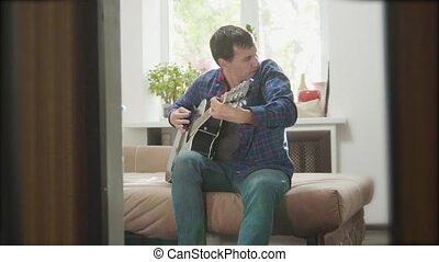 man guitarist playing music by wooden acoustic guitar. Man Playing Acoustic Guitar Close Up slow motion video. in the room sits on the couch lifestyle. man and guitar concept