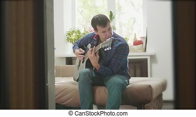 man guitarist playing music by wooden acoustic guitar. Man Playing Acoustic Guitar Close Up slow lifestyle motion video. in the room sits on the couch. man and guitar concept