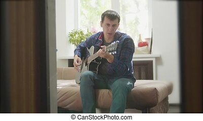 man guitarist playing music by wooden acoustic guitar. Man Playing Acoustic Guitar Close Up slow motion video. in the room sits on the couch. lifestyle man and guitar concept