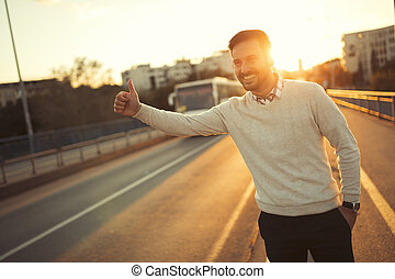 Man hailing a cab in sunset