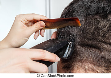 man haircut by clipper and comb - Brunette man getting a...