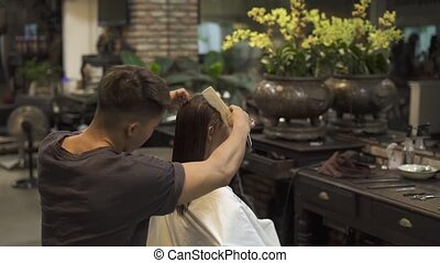 Man hairstylist brushing wet hair before female hairstyle in beauty studio. Hairdresser combing female hair with comb for cutting in hairdressing salon. Beauty and care concept.