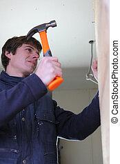 Man hammering a wall
