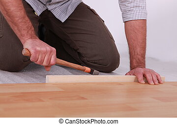 Man hammering laminate flooring into place