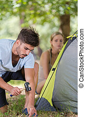 man hammering tent pegs in to the ground