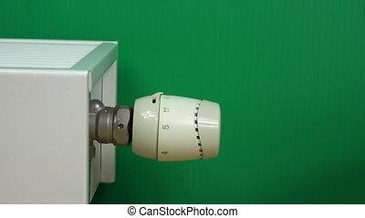 Man Hand Adjusting Temperature Of Radiator Thermostat on green.