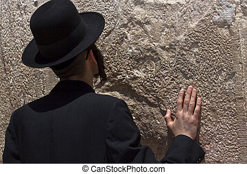 jewish religious man praying at the western wall with one hand on the wall