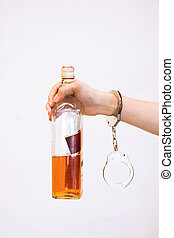 Man hand carrying alcohol drink with handcuffs - Drunk driving, alcohol addiction effect concept (Focus on Handcuffs)