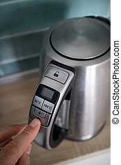 man hand click on the button iron electric kettle on the background of the kitchen
