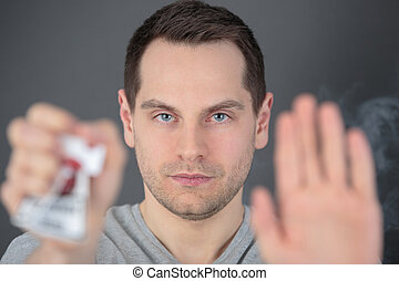 man hand crushing a packet of cigarettes stop smoking concept