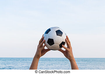 Man hand holding a soccer ball on the sky with sea